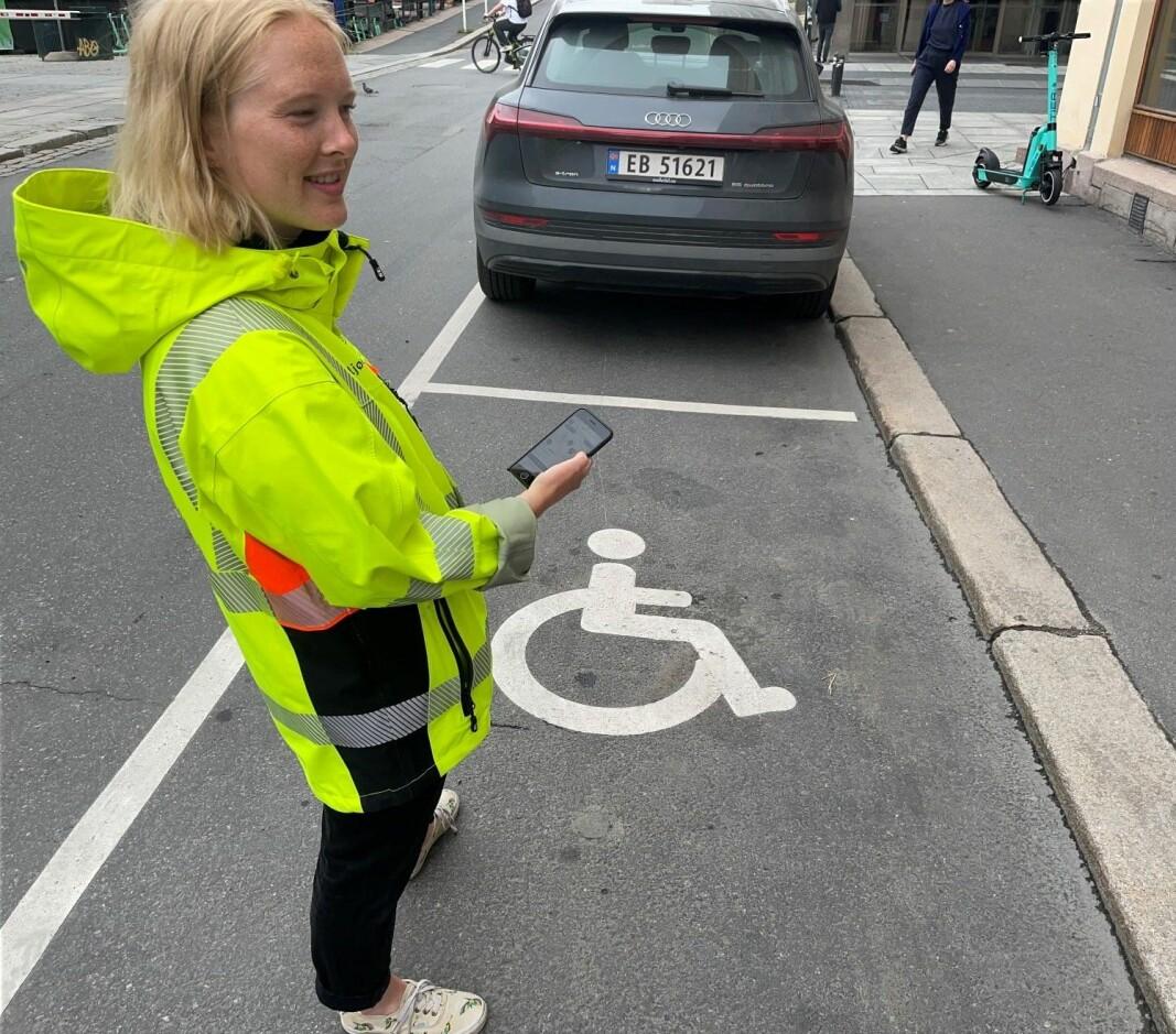 Prosjektleder Sesilie Bjørdal i bymiljøetaten står på en av plassene som inngår i prøveprosjektet. Den lyse sirkelen under HC-symbolet er området der sensorene som kommuniserer med Bil i Oslo- appen ble lagt i bakken i vinter.