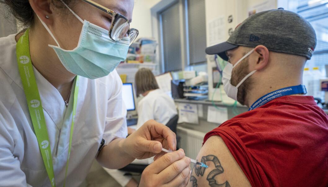 Portør Magnus Kinne får sin første sprøyte med Moderna-vaksine av sykepleier Andrea Navarrete på Vaksinasjonspoliklinikken ved Bedriftshelsetjenesten på Ahus.