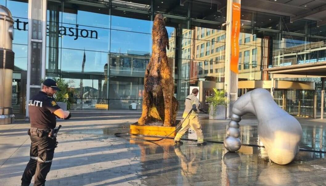 Brannvesenet etterslukker skulpturen av en ulende hund dekket av mose utenfor inngangen til Flytogterminalen og Oslo S.