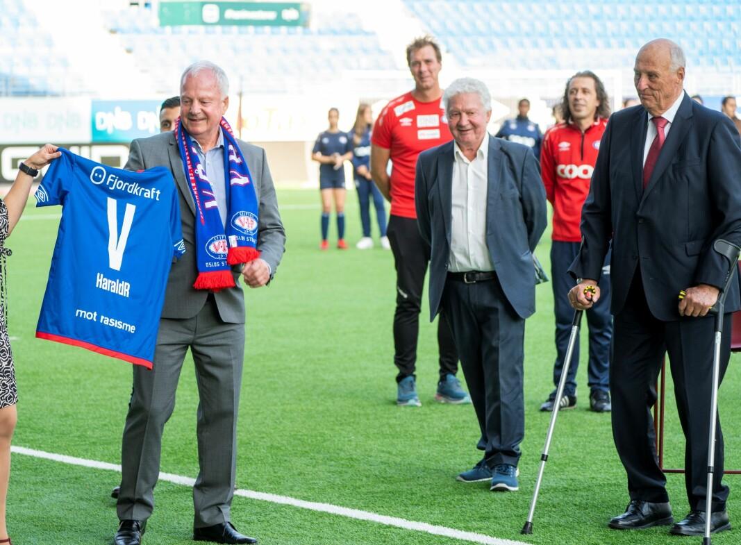 Mangeårige Vålerenga-spiller og styreleder, Rune Hansen, overrakte kong Harald den kongelige drakta fra klubben som spiller i kongeblått. Til høyre for Kongen står Åge Petter Christiansen