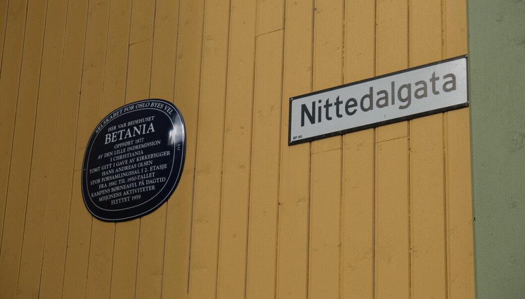 Det blå skiltet henger på veggen i Nittedalgata 8.