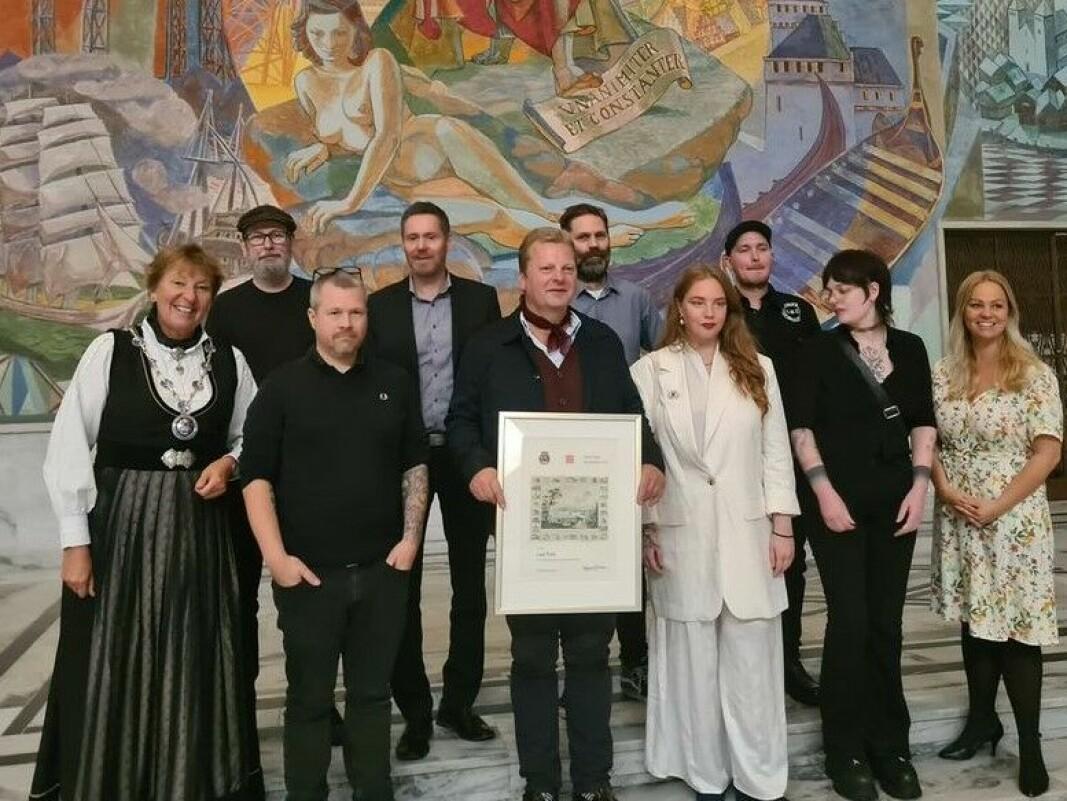 Daglig leder Martin Dynna og resten av LastTrain-staben i Rådhuset med synlig bevis på at rockebula har fått Oslo bys kunstnerpris. Til venstre ordfører Marianne Borgen (SV) og ytterst til høyre leder av bystyrets kulturutvalg, Eivor Evenrud (Rødt).