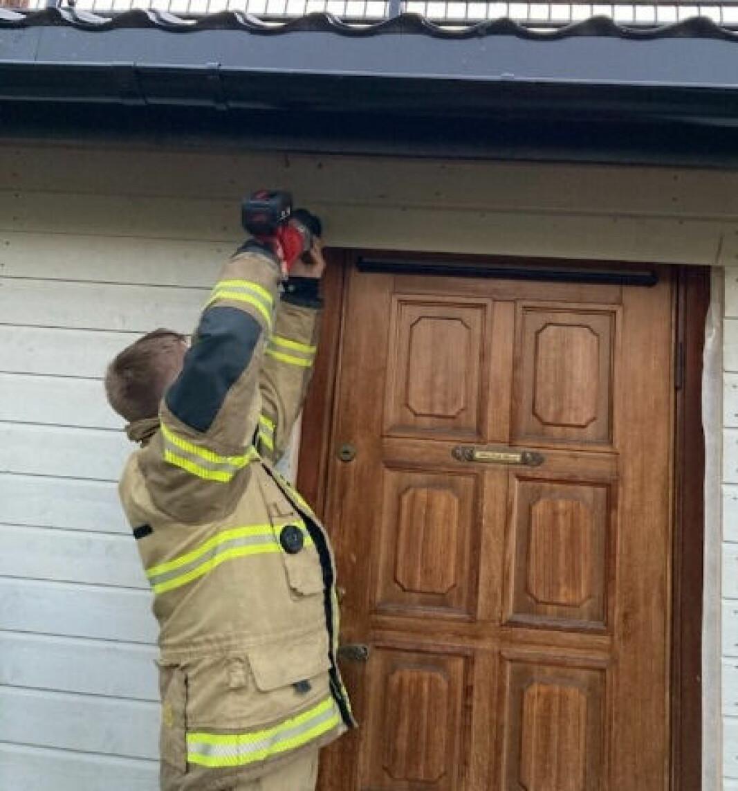 Her skjærer brannvesenet fem-seks centimeter av panelet så beboerne i huset kom seg ut.