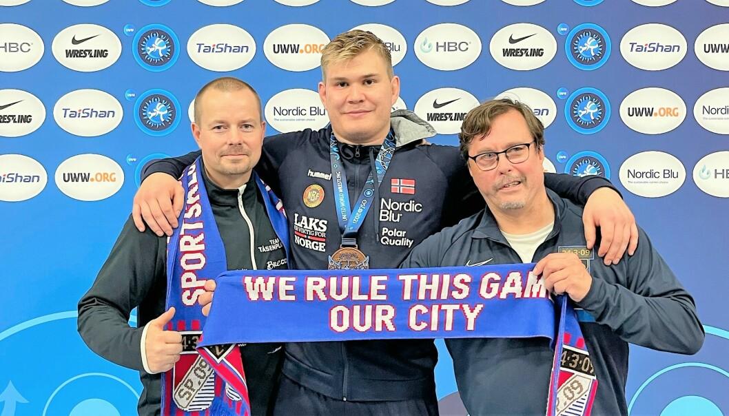 Bronsevinner Oskar Marvik feirer med leder for Sportsklubben 09 bryting, Håvard Solli Bergheim (t.v) og nestleder Jørgen Johansson etter bronsekampen i bryte-vm lørdag kveld.