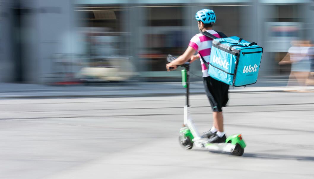 En matbud fra Wolt kjører elsparkesykkel i Oslo sentrum.